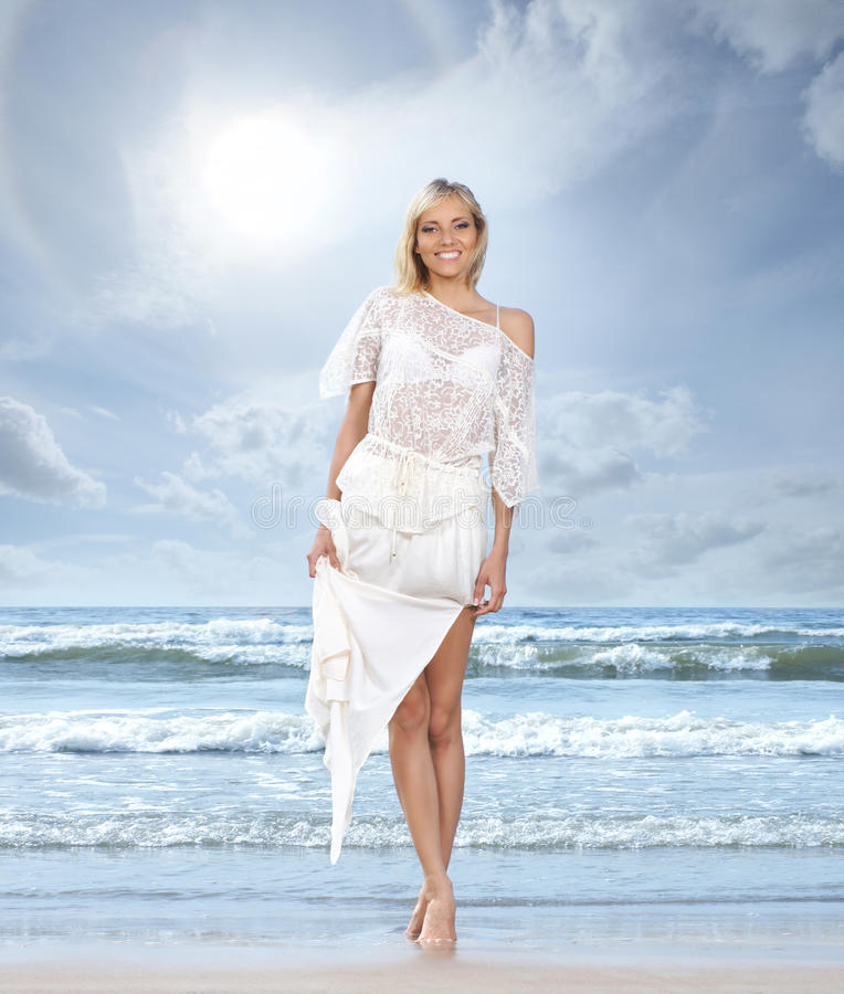 A young woman in a white dress on a beach background royalty free stock image