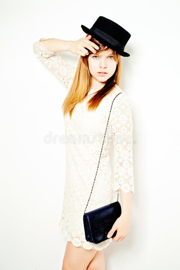 Young Woman in White Dress and Black Hat Posing. Young Woman in White Lace Dress and Black Hat Posing stock images