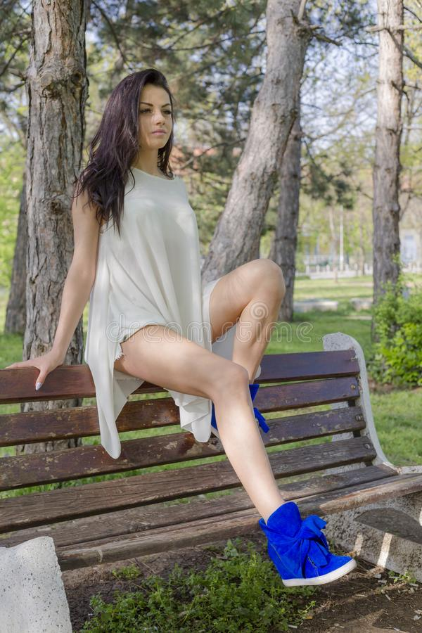 Young woman in white dress and blue suede shoes sitting on wooden bench in park stock photos