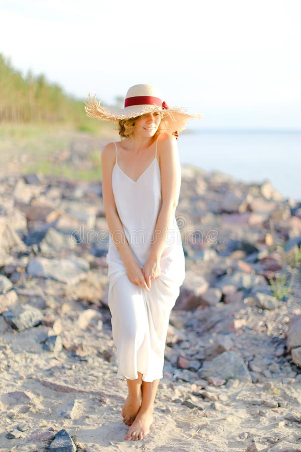 Back view of woman walking on. Young woman in white dress and hat with red ribbon standing on shingle beach. Concept of summer vacations and resort royalty free stock image