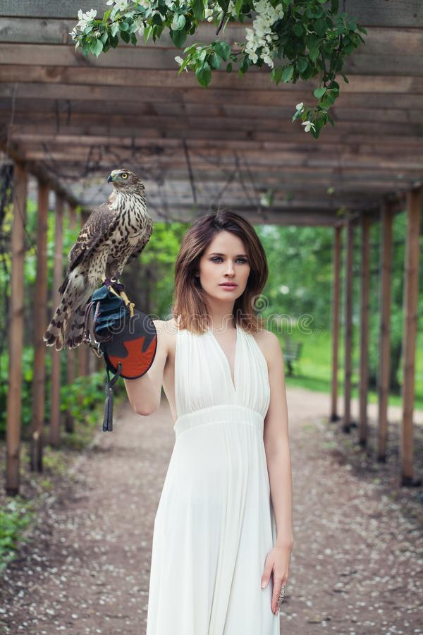 Young woman in white dress holding hawk bird outdoor.  royalty free stock photography