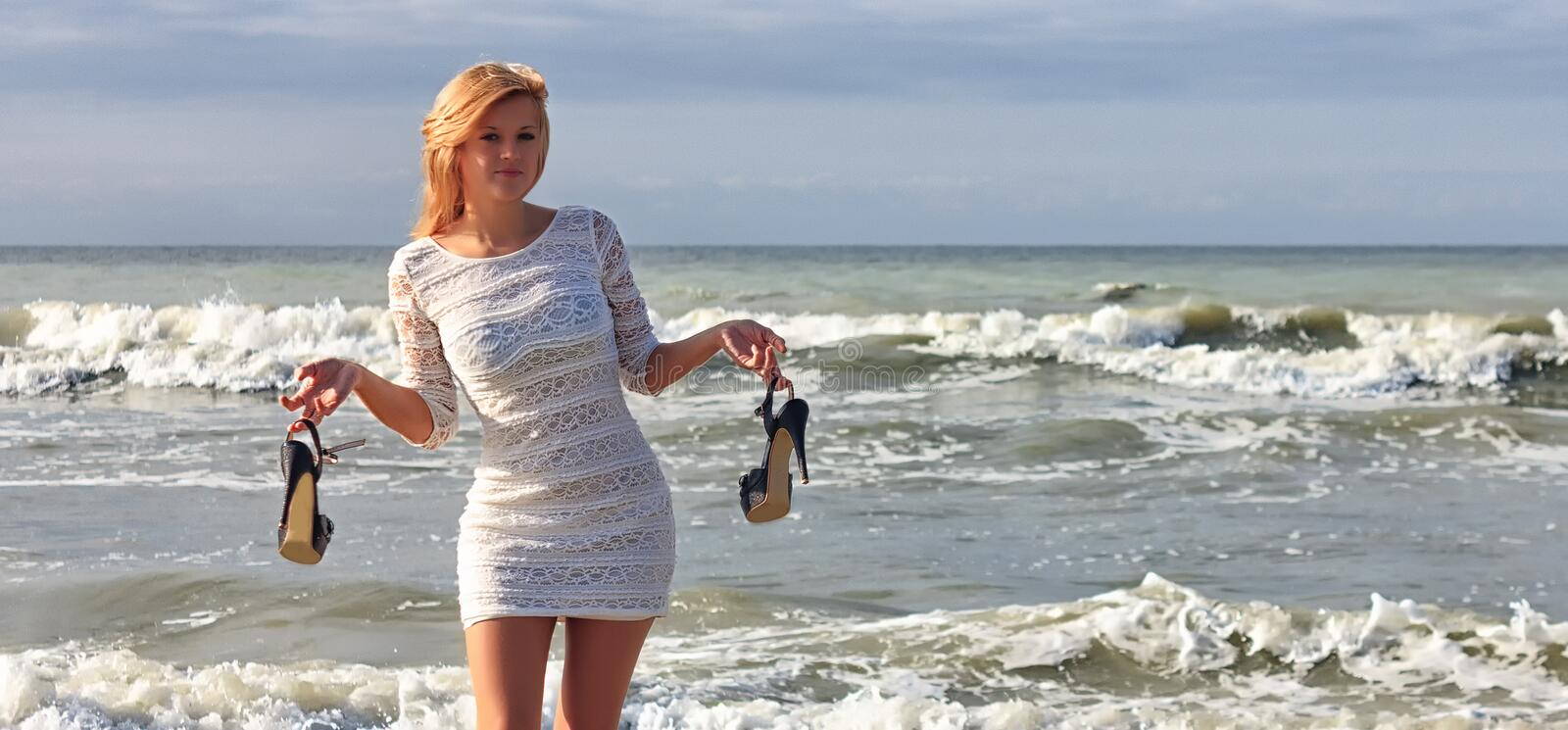 Young woman in white dress holding his high heels shoes, standing on beach with sea waves stock photo