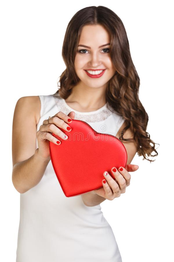Young woman in white dress holds heart shaped box. royalty free stock photography