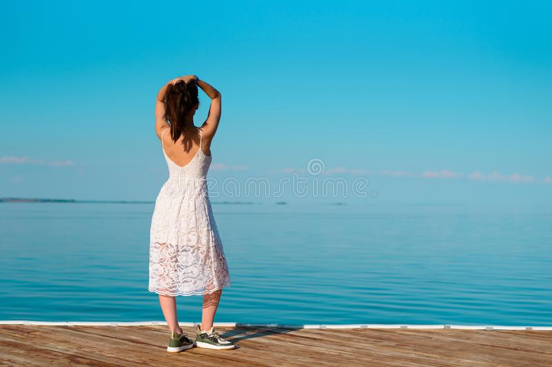 A young woman in a white dress stands on a wooden pier with her hands on her head looking into the distance stock image