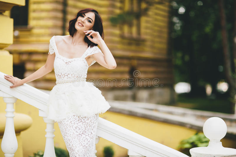 Young woman in white dress on the street stock photos