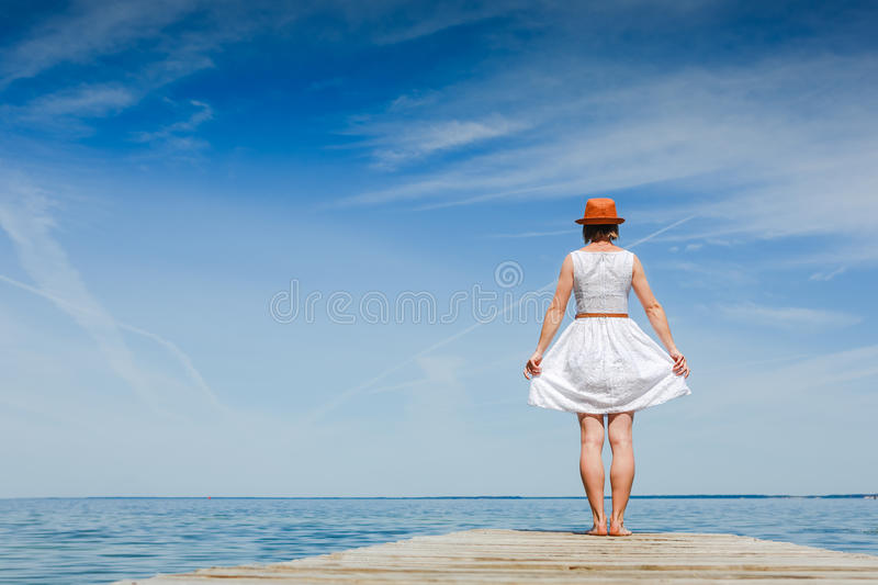 Young woman in white dress sunbathing at the seaside. Summer vacation stock images