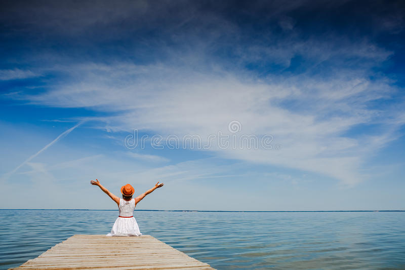 Young woman in white dress sunbathing at the seaside. Summer vacation royalty free stock photography