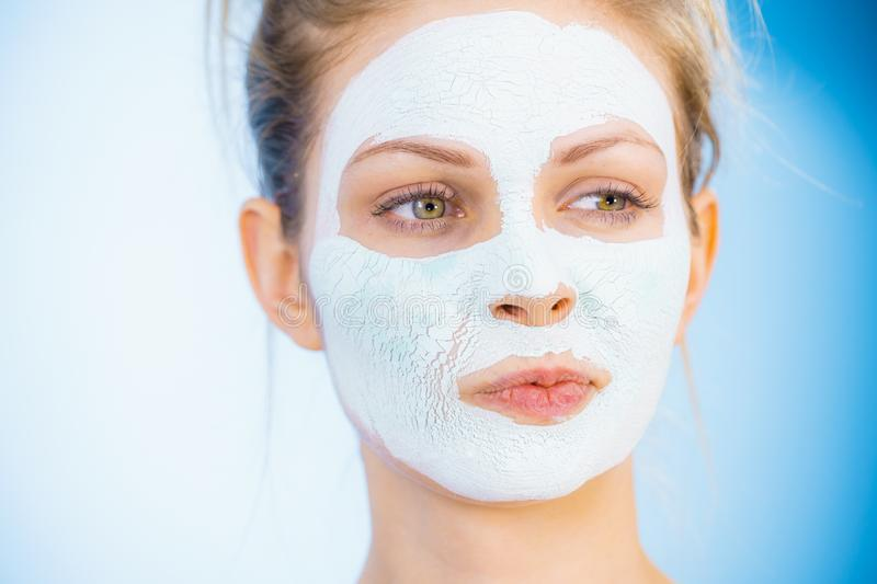 Girl with dry white mud mask on face. Young woman with white dry mud mask on face, against blue. Teen girl taking care of oily skin, cleaning the pores. Beauty stock image