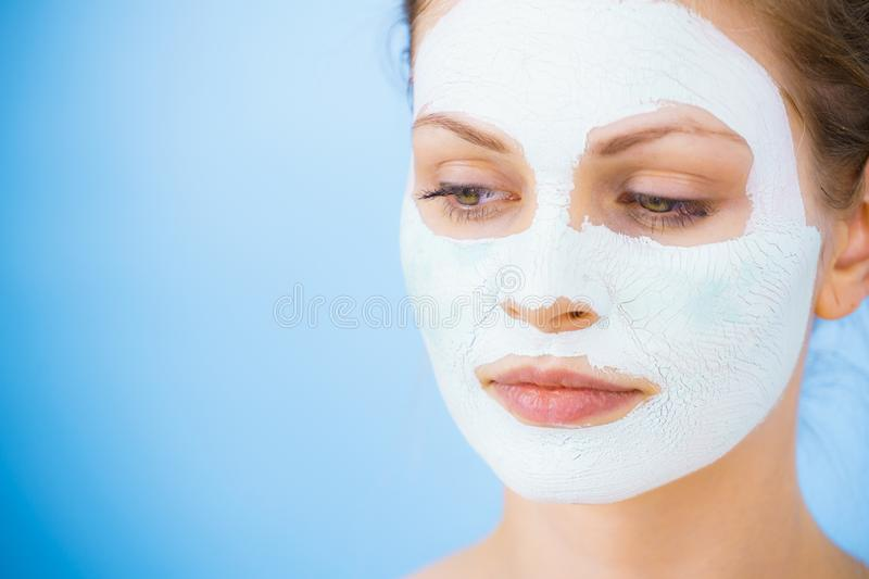 Girl with dry white mud mask on face. Young woman with white dry mud mask on face, against blue. Teen girl taking care of oily skin, cleaning the pores. Beauty stock photography
