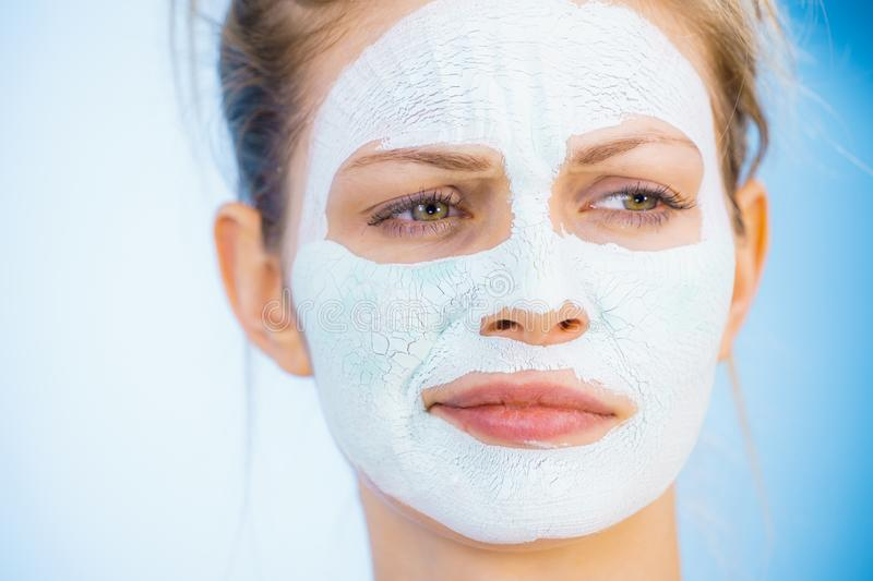 Girl with dry white mud mask on face. Young woman with white dry mud mask on face, against blue. Teen girl taking care of oily skin, cleaning the pores. Beauty royalty free stock photos