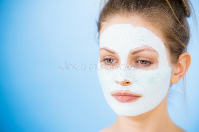 Girl with dry white mud mask on face. Young woman with white dry mud mask on face, against blue. Teen girl taking care of oily skin, cleaning the pores. Beauty stock images