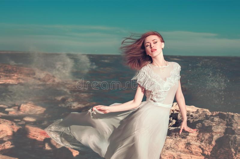 young woman in white fluttering dress is standing on the sea coast near the big stone. royalty free stock photos