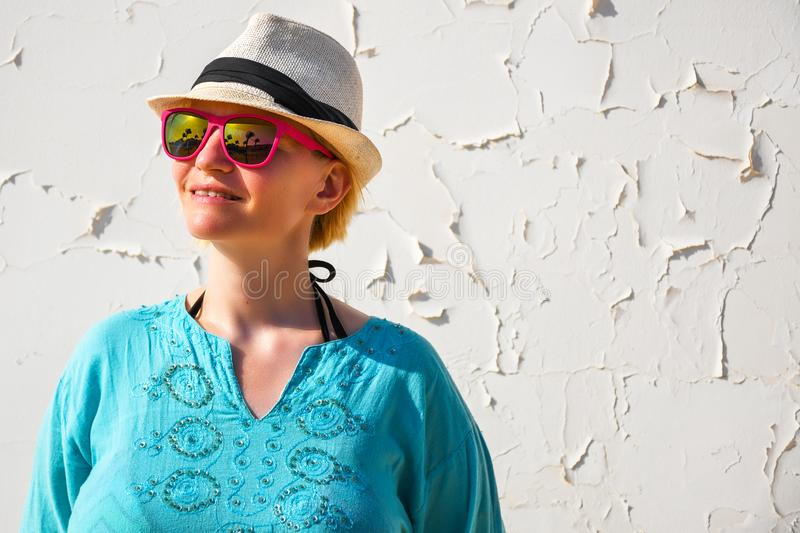 Young woman with white hat and pink sunglasses dressed in beautiful blue shirt relaxing royalty free stock image