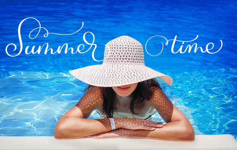 Young woman in white hat resting in pool and text Summer time. Calligraphy lettering hand draw royalty free stock images
