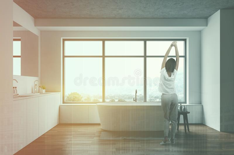 Young woman in white luxury bathroom. Young woman in pajamas standing in modern bathroom with white and wooden walls, comfortable bathtub and double sink. Toned stock photography