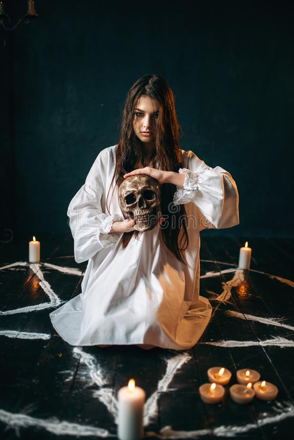 Woman holds human skull in hand, dark magic, witch stock photography