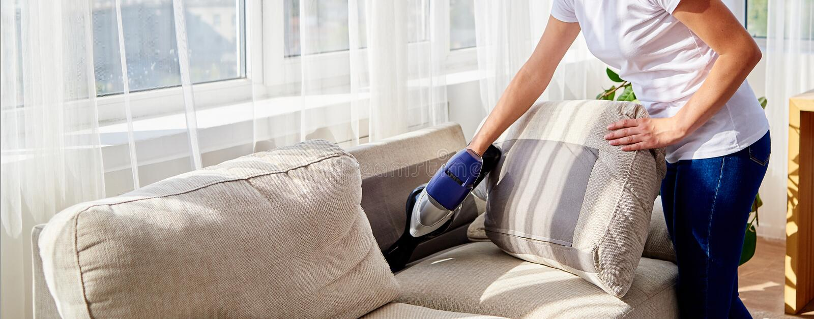 Young woman in white shirt and jeans cleaning sofa with vacuum cleaner in living room, copy space. Housework, spring-cleaning stock image