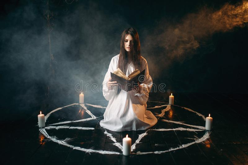 Woman sitting in the center of pentagram circle. Young woman in white shirt sitting in the center of pentagram circle with candles and reads a spell, black royalty free stock photography