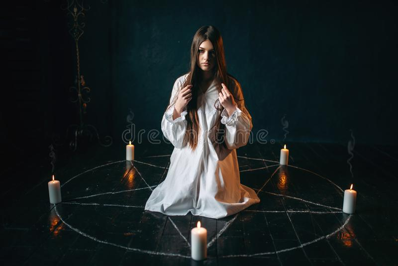 Woman sitting in the center of pentagram circle. Young woman in white shirt sitting in the center of pentagram circle with candles and reads a spell, black stock image