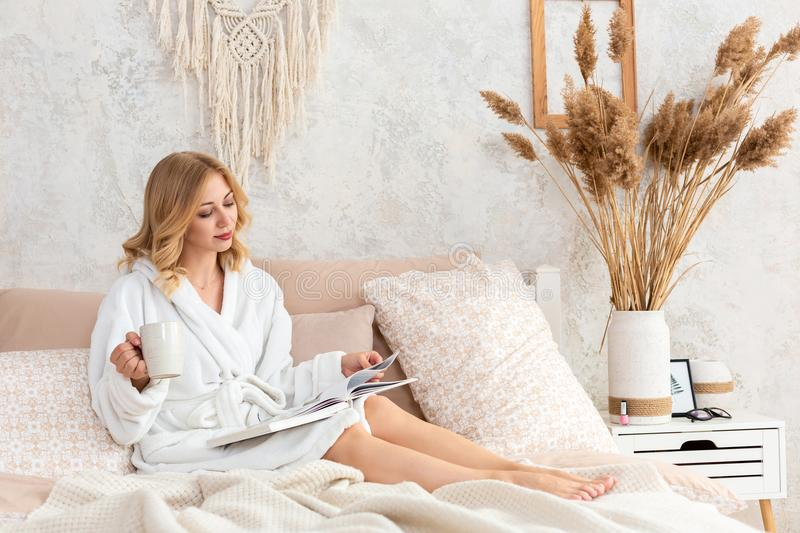 Young woman in white terry robe is drinking coffee and reading magazine or book in bedroom. royalty free stock image