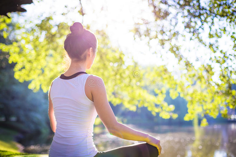 Young woman in white top practicing yoga in beautiful nature. Meditation in morning sunny day stock image
