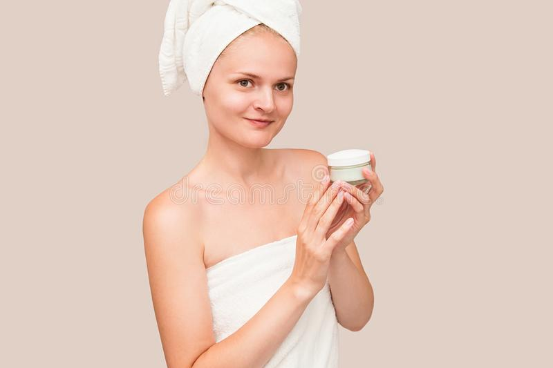 Young woman in white towel apply moisturizer cream on bright isolated background. Skin care, spa concept royalty free stock photos