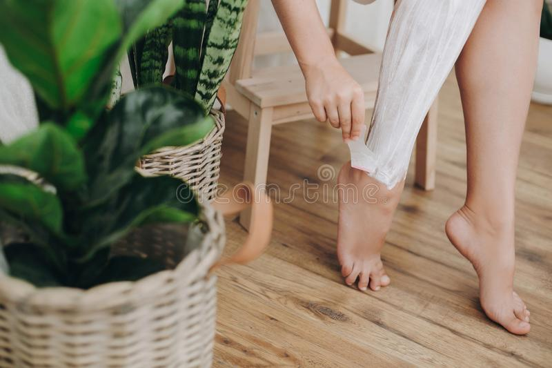 Young woman in white towel applying shaving cream on her legs in home bathroom with green plants. Skin care and wellness concept. Hand holding plastic razor on stock photography