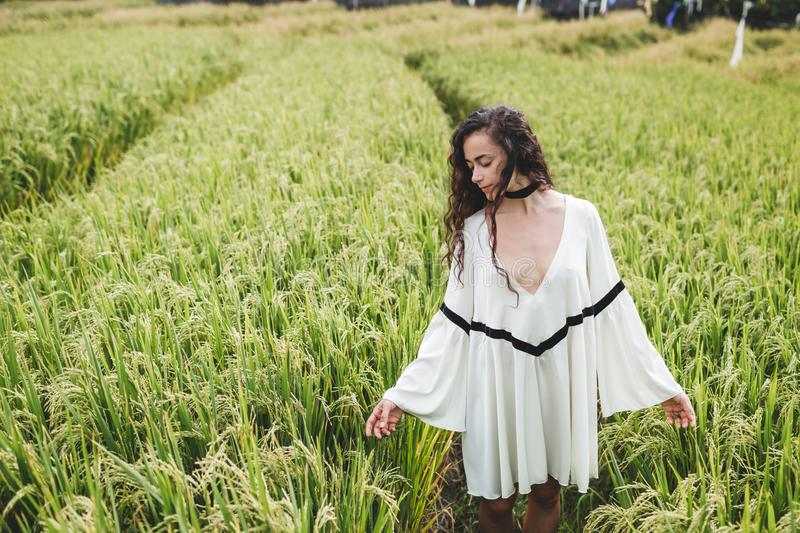 Woman in white tunic in rice fields Bali Tegallalang. Rustic Ubud village. Young woman in white tunic in rice fields Bali in Tegallalang. Rustic Ubud village stock photography