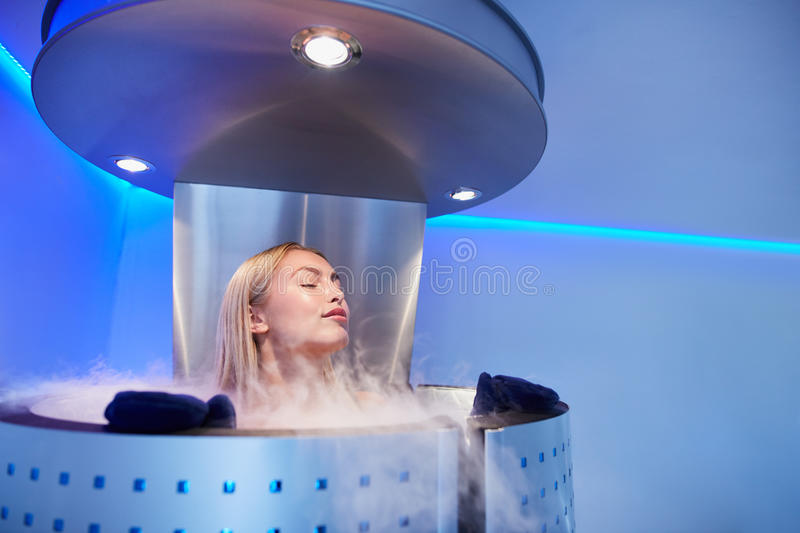 Young woman in a whole body cryo sauna. Portrait of young woman in a whole body cryo sauna. Female getting cryo therapy at the cosmetology clinic royalty free stock image