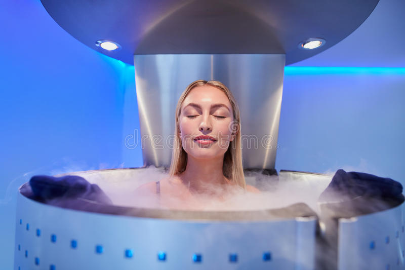 Young woman in a whole body cryotherapy cabin. Portrait of happy young woman in a whole body cryotherapy cabin with her eyes closed. Cryosauna chamber for stock photos