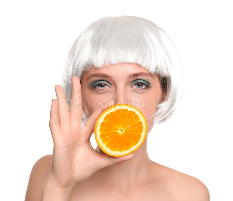 Young woman with wig and orange half on white background royalty free stock photography