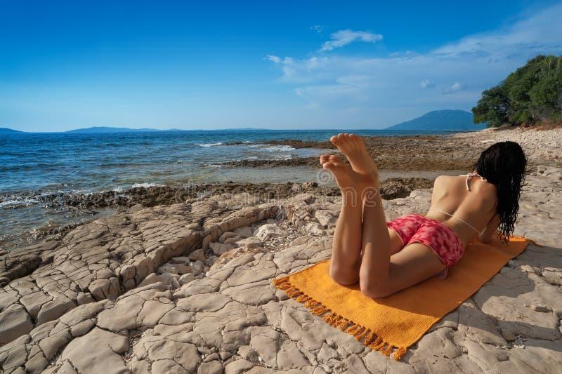 Young woman on wild island beach stock photo
