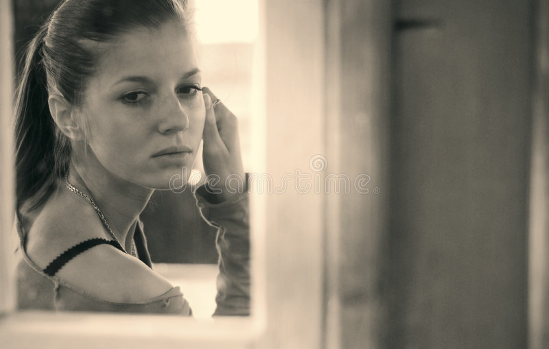 Young woman and window stock images