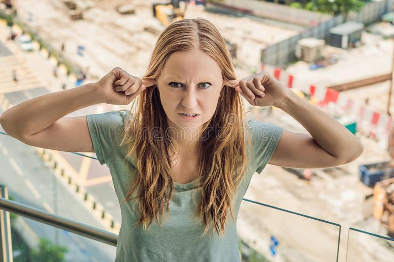 A young woman by the window annoyed by the building works outside. Noise concept.  royalty free stock photography