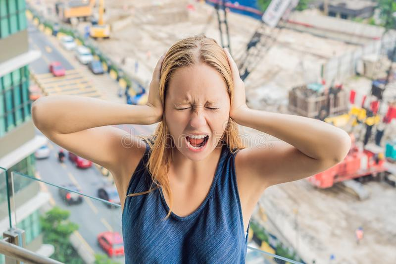 A young woman by the window annoyed by the building works outside. Noise concept.  royalty free stock photos