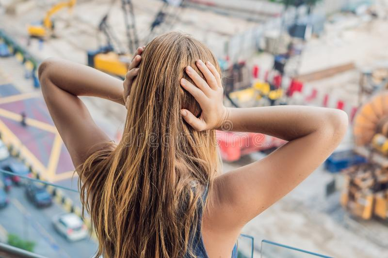 A young woman by the window annoyed by the building works outside. Noise concept.  stock photo