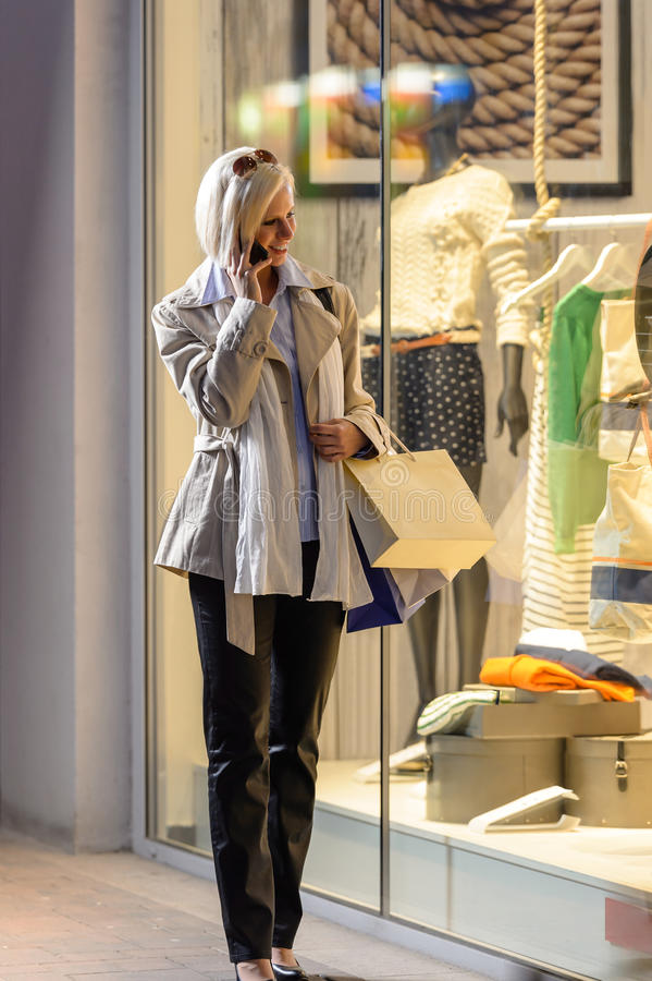 Young woman window shopping evening city stock image