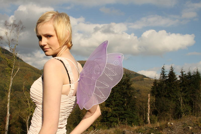 Young woman with wings against bright blue sky. Young attractive blonde haired woman with purple fairy wings in a barren landscape with a bright blue sky stock image