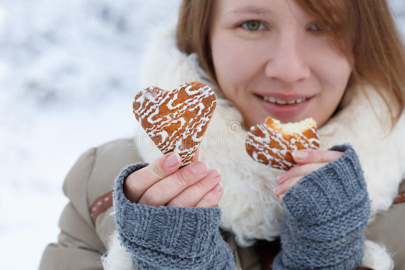 Young woman in winter coat and knitted grey mittens hold beautiful heart shaped biscuit cookies, one bitten, with white icing. At snow background. Shallow dof royalty free stock image