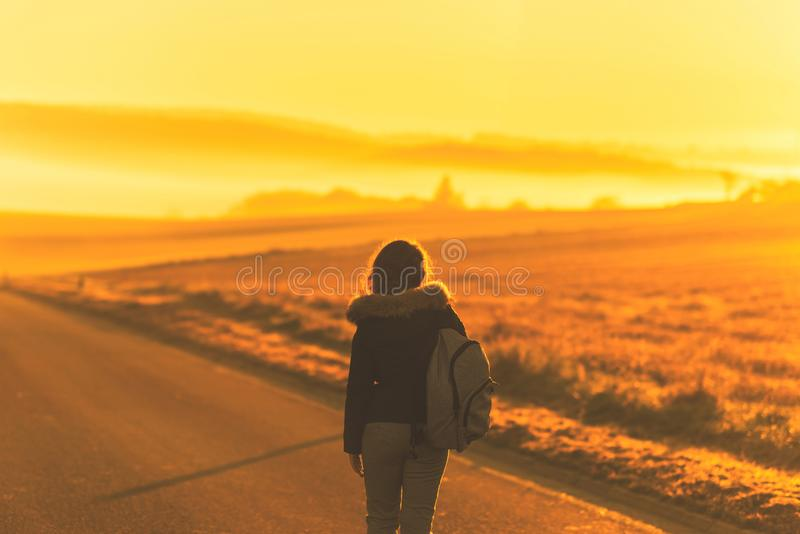 Young woman in the winter jacket with a backpack on the road against the background of the sunrise autumn field. Travel and tourism concept royalty free stock photos