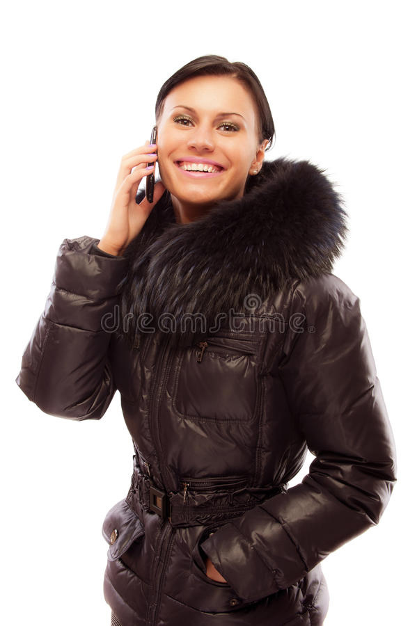 Young woman in a winter jacket speaks on phone