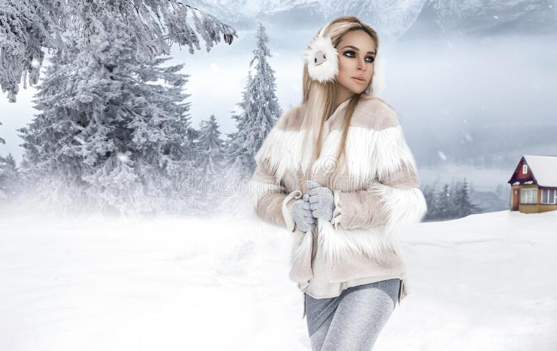 Young woman winter portrait. Winter fashion model. Attractive young woman in wintertime outdoor. Mountains, white snow in magic. Winter day royalty free stock images