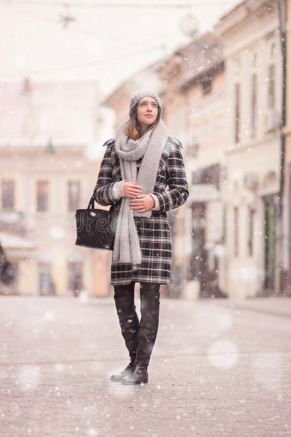 Young woman winter snowing looking above royalty free stock image