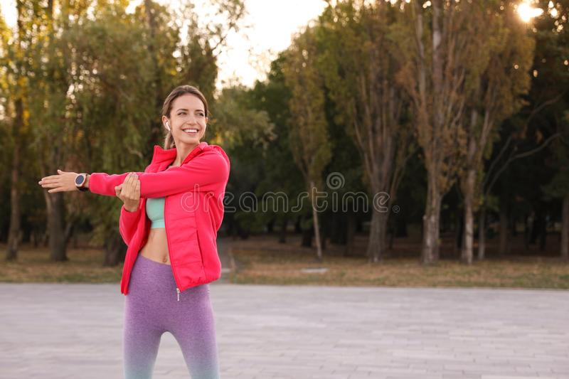 Young woman with wireless headphones listening to music while exercising. Space for text stock photos