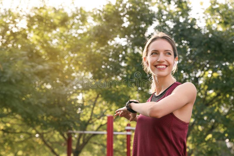 Young woman with wireless headphones listening to music while exercising on sports ground stock photos