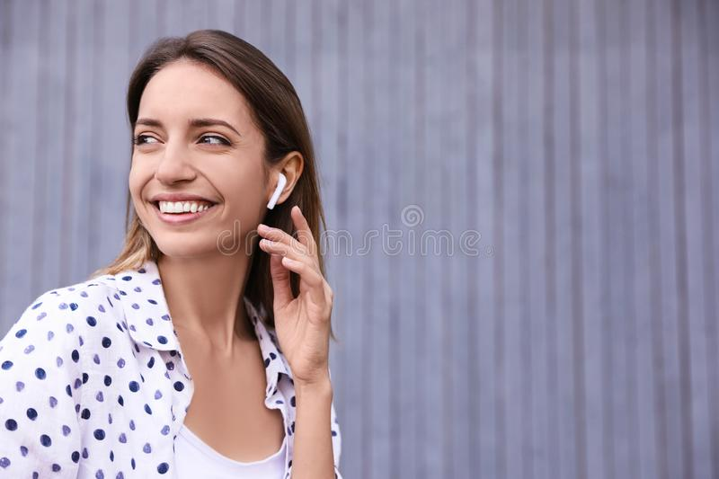 Young woman with wireless headphones listening to music near wall. Space for text royalty free stock image