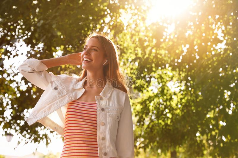 Young woman with wireless headphones listening to music in park stock image