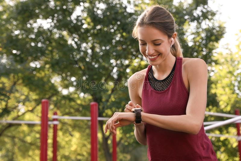 Young woman with wireless headphones and smart watch listening to music royalty free stock photo