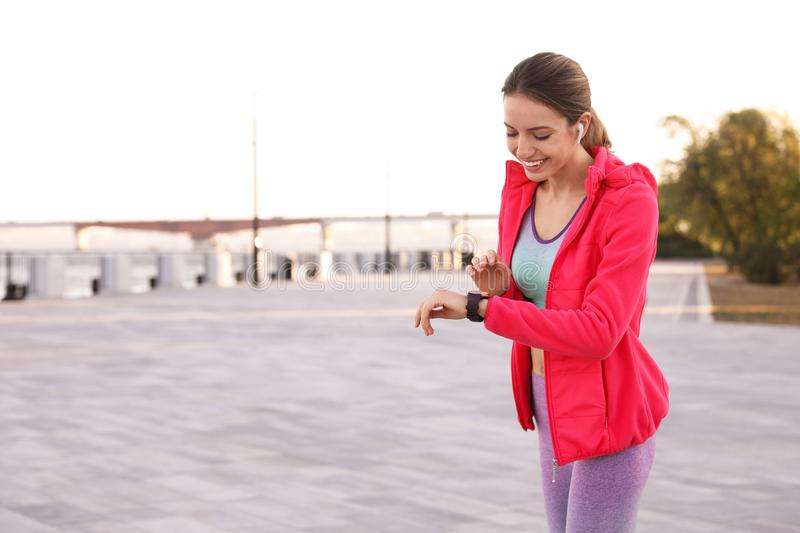 Young woman with wireless headphones and smartwatch listening to music. Space for text stock photos