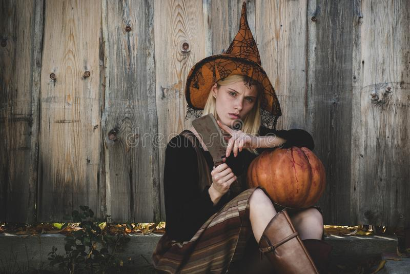 Young woman with witch hat dressed as vampire for Halloween party. Vampire woman on Halloween night. Smiling woman in stock image
